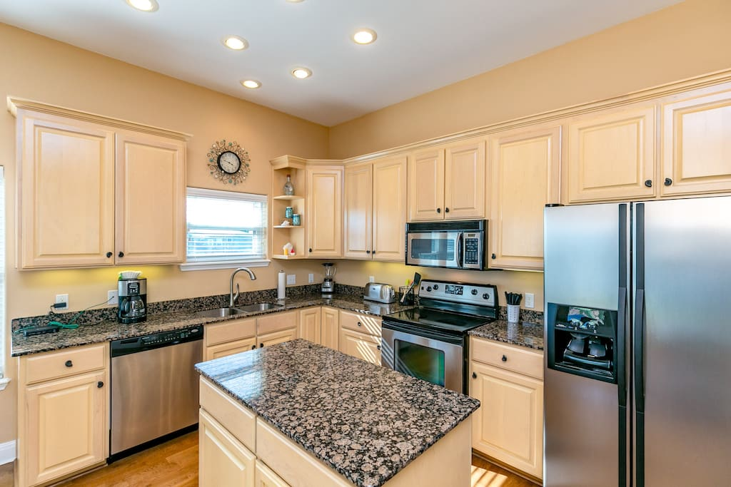 The kitchen features a stainless steel fridge, microwave, stove/oven and dishwasher.