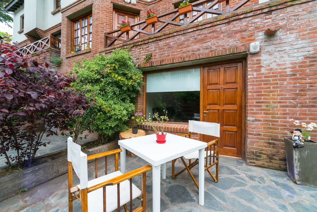 Patio privativo c jardín, mesa y sillas