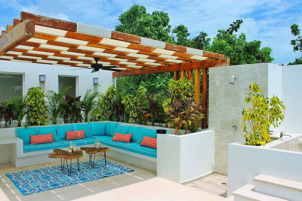 Second floor outdoor living room with shaded pergola, shower and jacuzzi
