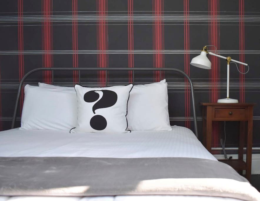 The Queen-sized bed is up against a full wall covered in modern plaid wall paper