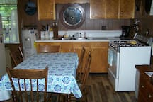 Fully equipped kitchen has a full refrigerator, stove, microwave, coffee maker, toaster, dishes, pots and pans