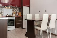 kitchen with stove, fridge and dining area for 4 people