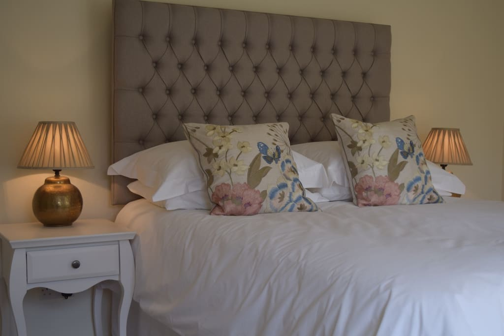 Master bedroom with kingsize bed and luxury bedding