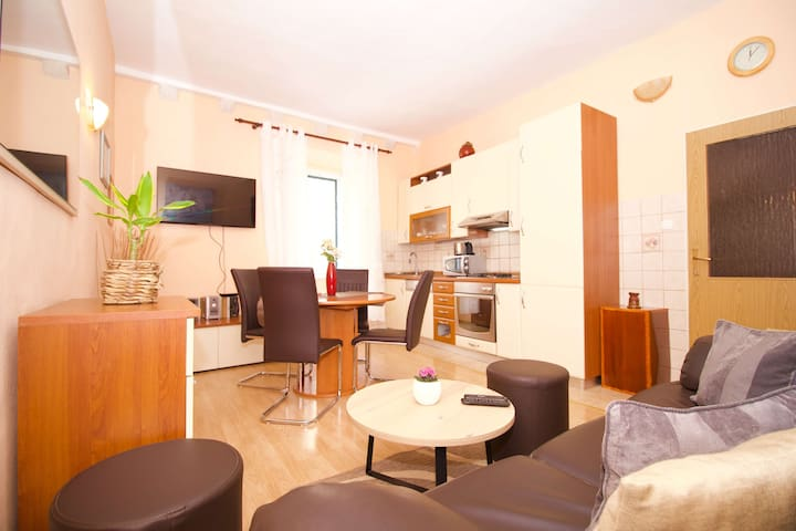 Open kitchen/living area with sofa, dining table for 4, satellite TV and radio/cd player.