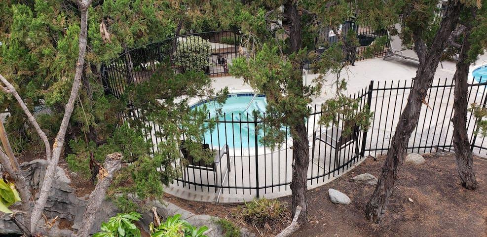 Balcony overlooks pool and jacuzzi