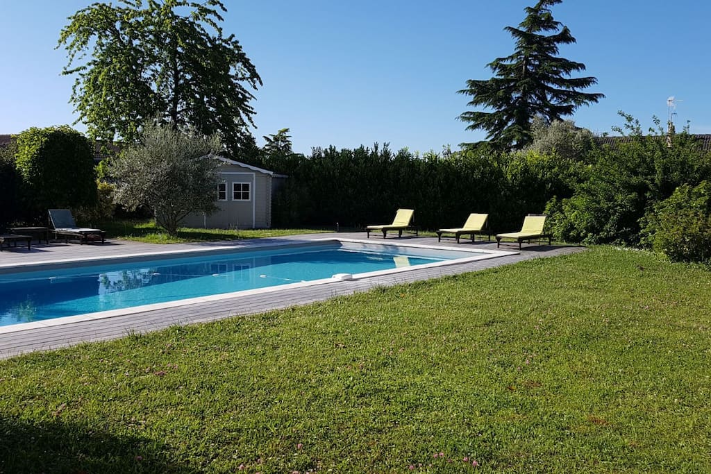 Piscine vue du salon avec le petit chalet servant de pool house (avec un frigo d'appoint) idéal pour les affaires de piscine et se changer avant le bain