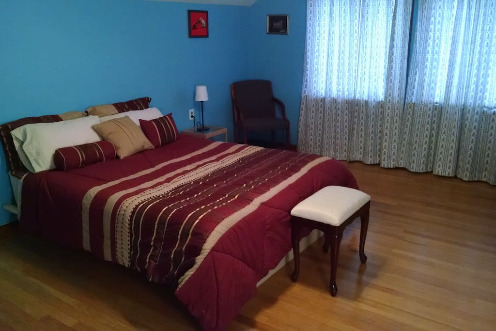 Queen bed with side tables, and upholstered stool. Outlets near bed for charging phones.
