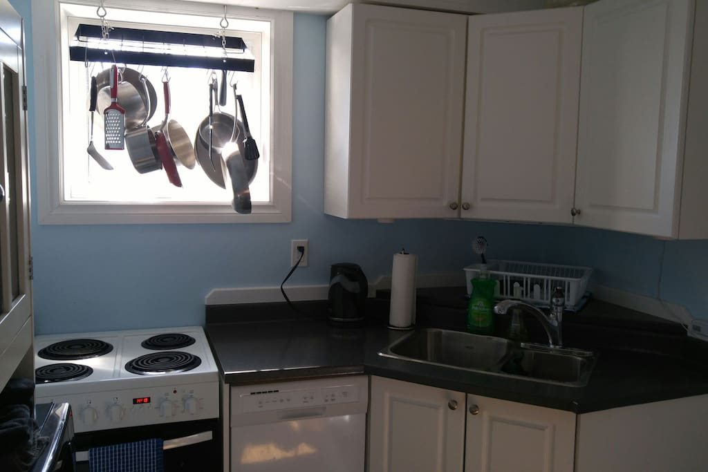 Fully equipped kitchen with stove, oven, dishwasher, fridge, microwave, small appliances