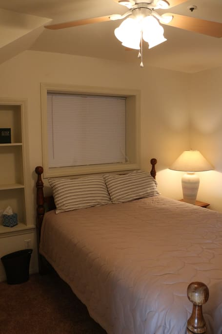 Bedroom with queen size bed, ceiling fan and light