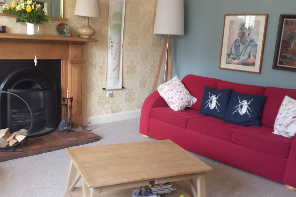 Main lounge with open fireplace. Showing red sofa bed, sleeps 2.