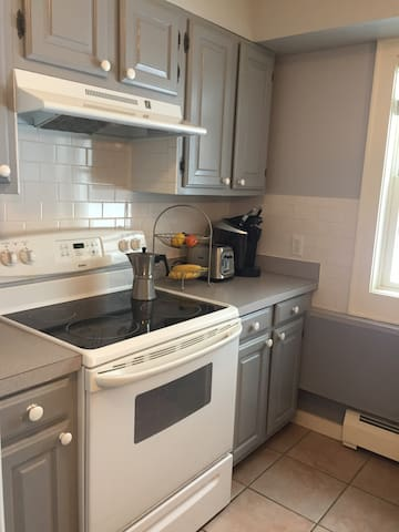 Kitchen with stove, Keurig, dishwasher, toaster and microwave.