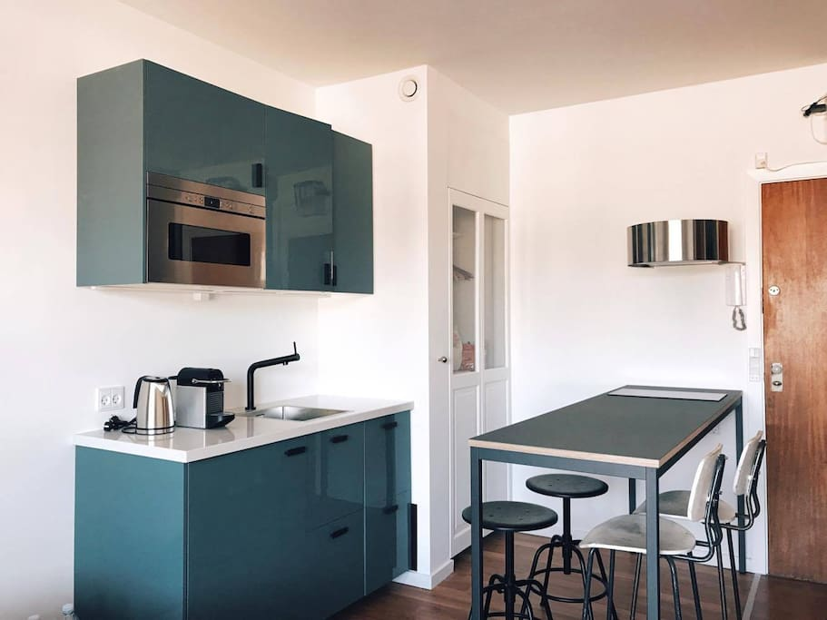 Modern, industrial-designed kitchen with refrigerator, microwave, coffee, tea, hotplate, and a dinner table for four.