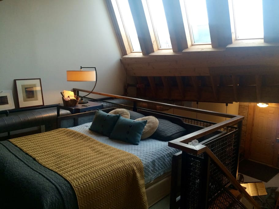 Queen size bed lit by sunny sawtooth skylights.  Lofts are loved for their beautiful light.