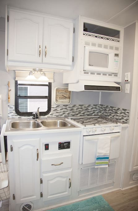 Kitchen is fully stocked with pots, pans, glassware, utensils, and dishes.