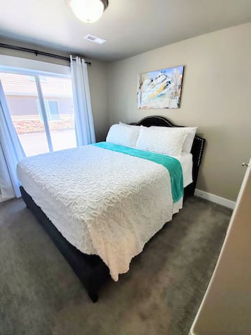 Main floor bedroom with Cal King bed, beautifully decorated with mountain scenes and wildflowers by local Ogden artist Emily Cook.