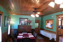 Dining and serving area for 6+ complete with 100 yr. old upright piano.  Bath and Laundry are through the door.
