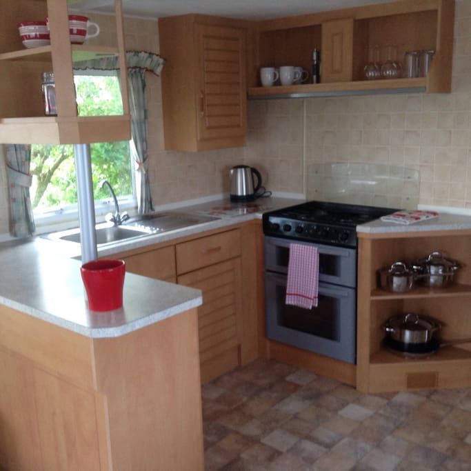Kitchen with gas oven and hob, microwave, fridge, kettle and toaster. Pans, cutlery, crockery and glassware.