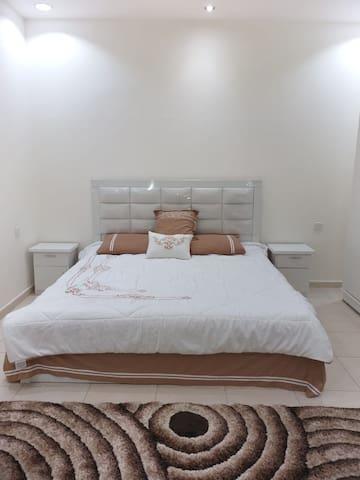 غرفه النوم الرئيسيه وبها سرير كبير الحجم مزدوج يسع الي فردين