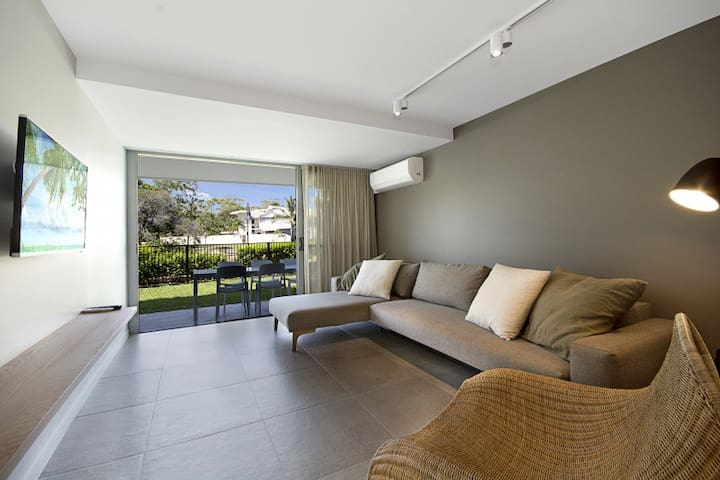 ground floor riverview apartment with glass sliding doors opening up to manicured lawn and Noosa River views