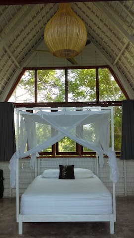 comfortable bedroom with seating and clothes storage area all looking toward pool and ocean