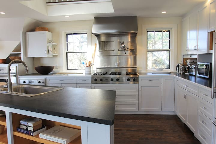 Kitchen enjoys 6 burner gas stove top, two ovens and classic sub zero refrigerator
