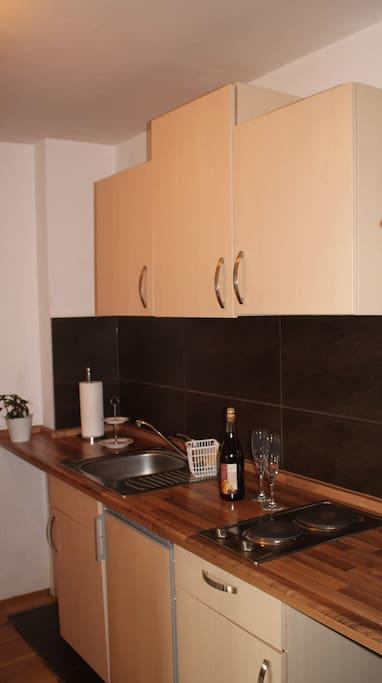 Küchenzeile mit zwei Herdplatten, Wasserkocher und Kühlschrank mit kleinem Gefrierfach.