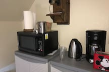 Mini kitchen includes full size refrigerator, microwave, coffee maker, toaster, hot water maker, cabinets with plates, bowls, cups, silverware.