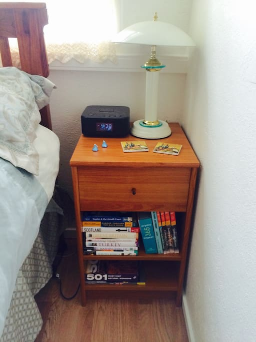 Nightstand with touch lamp and brochures to browse for your travel adventures.
