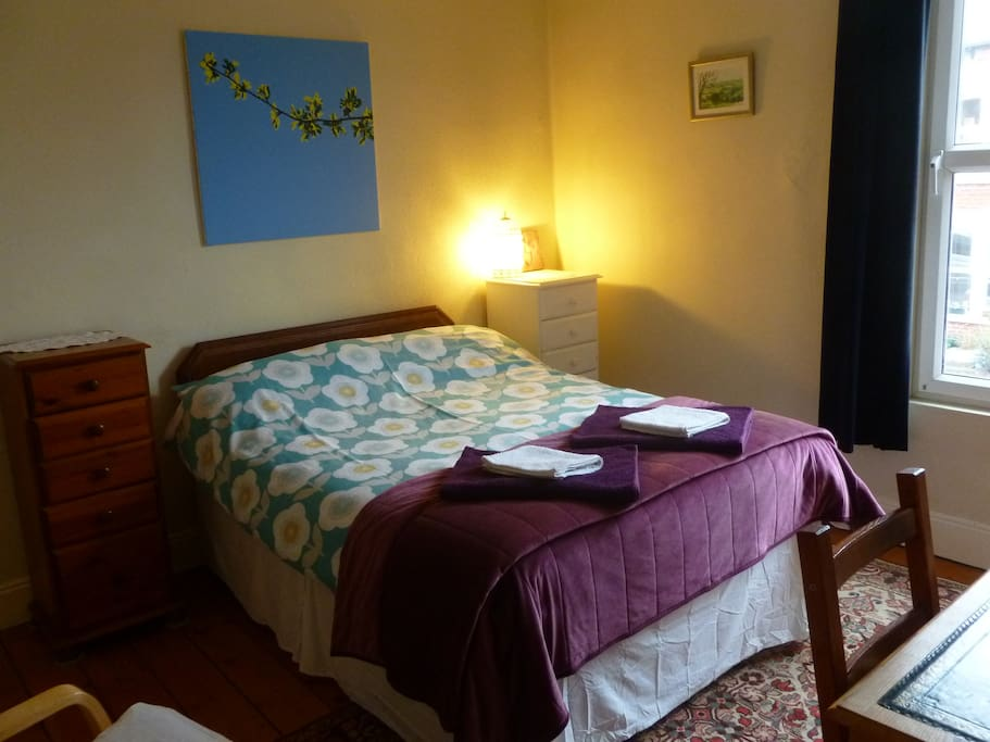 A very comfortable double bed, blackout curtains, a desk to work at and chair to relax in.