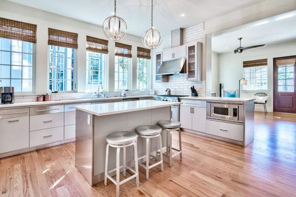 The modern kitchen has plenty of counter space and great lighting.