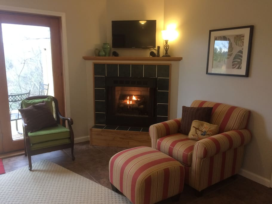 Living room with private deck and fireplace.  Unwind on the leather sofa or cozy up next to the fire in the club chair. Dish Satellite TV, Gas Fireplace. Kitchenette to the right of the chair.