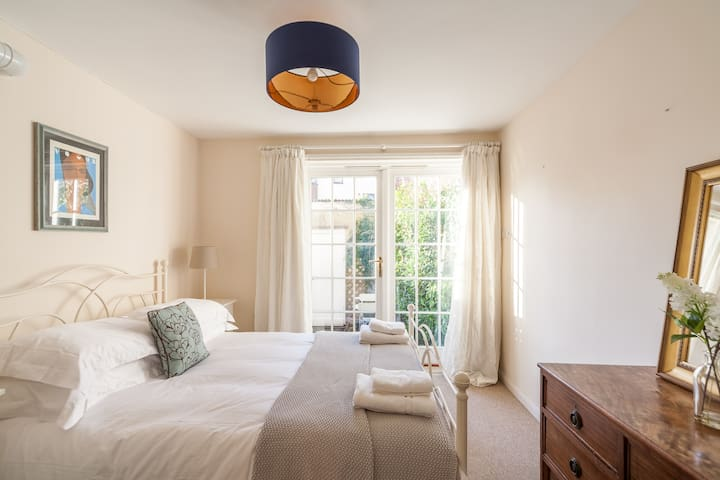 A cosy, light-filled second bedroom which opens onto the private courtyard at the rear.