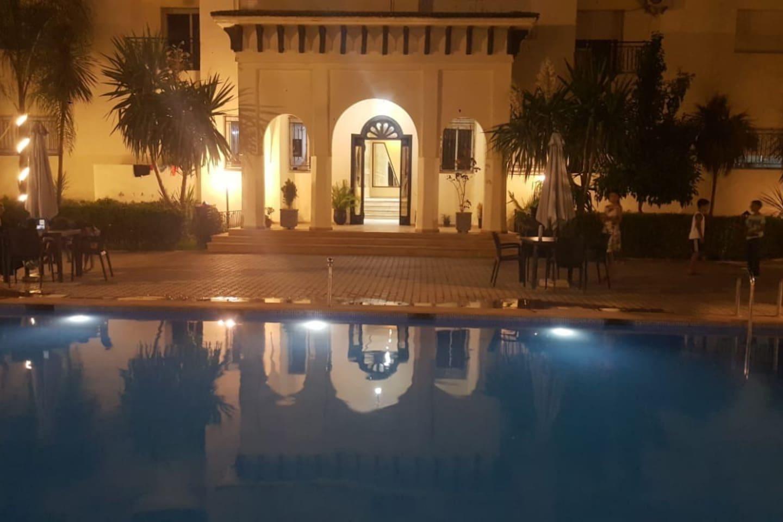Porte d'entrée donnant sur La piscine qui est située au milieu du Riyad, entourée de jardinets avec des plantes luxuriantes.