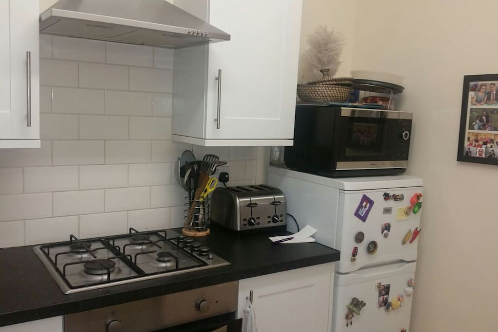 CLean and modern kitchen with utensils and use of the fridge and cooker.