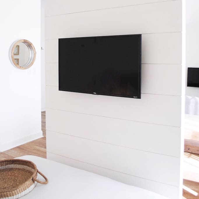 Room divider creates a sense of separation between bedroom and rest of the space.  Smart TV offers different viewing options than just cable.