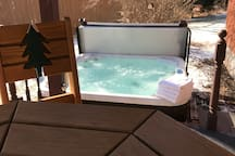 Hot Tub is just off of the covered deck which has an awesome pub style table and swivel pub chairs