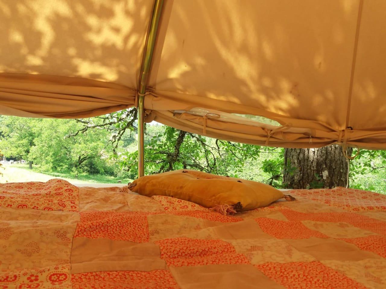 Un lit confortable dans une tente nomade en pleine nature avec possibilité de fermeture ou d'ouverture du pourtour de la tente pour plus de vue et de fraîcheur...