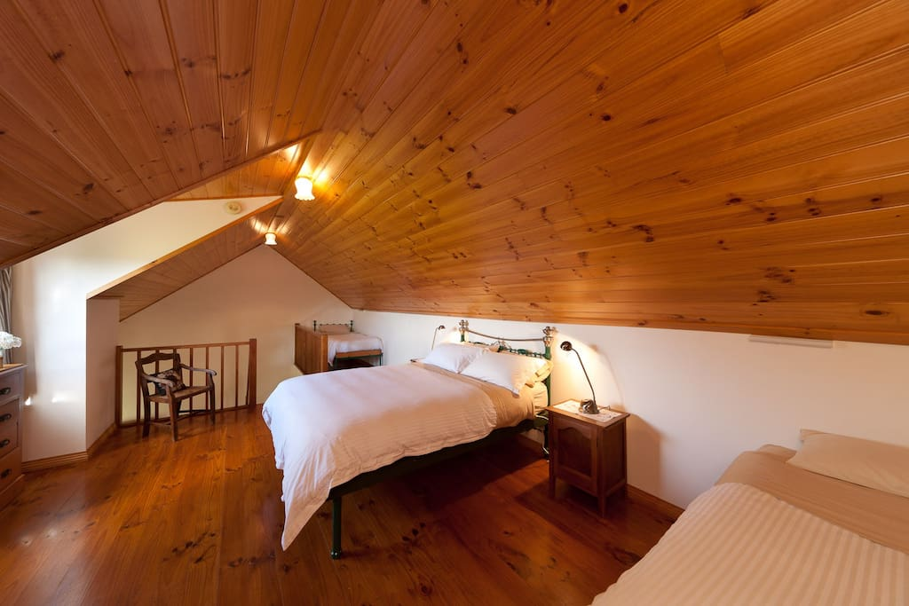 Loft bedroom with one queen bed and 2 single beds