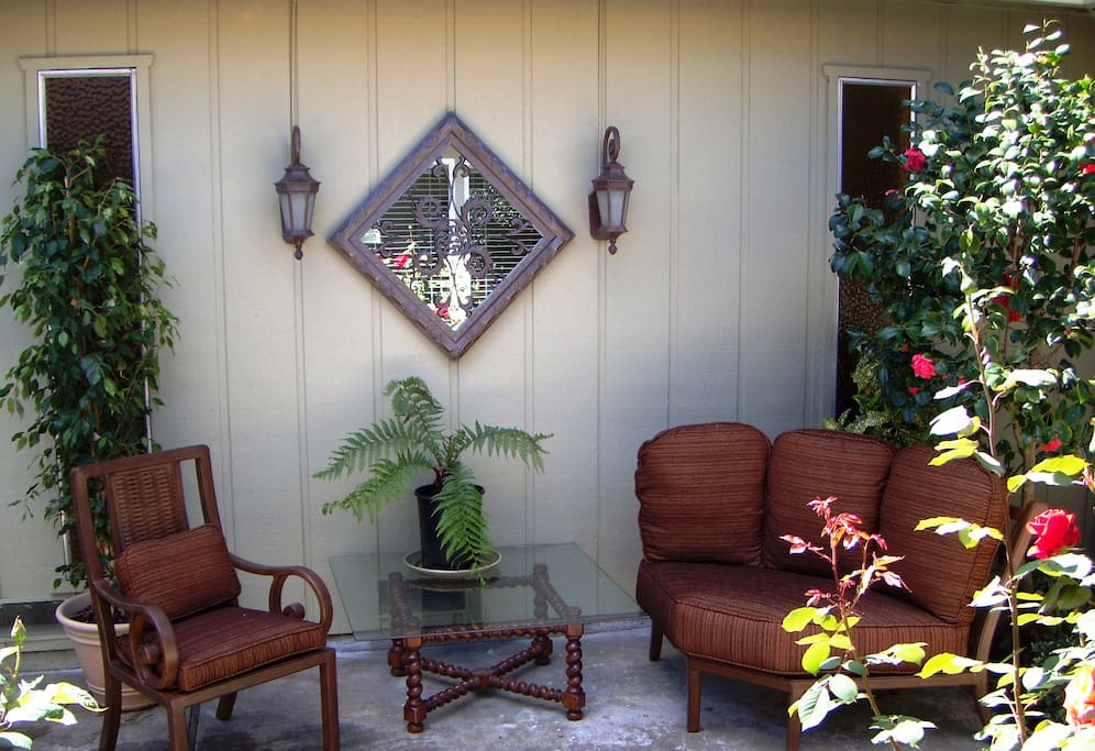 Private patio is lined with ornamental plants and comfortable seating.