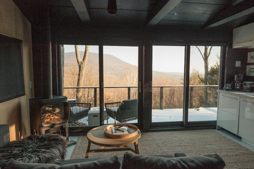 The main living space has a kitchen, couch, propane fireplace and dining nook with a view of Mombaccus Mountain.