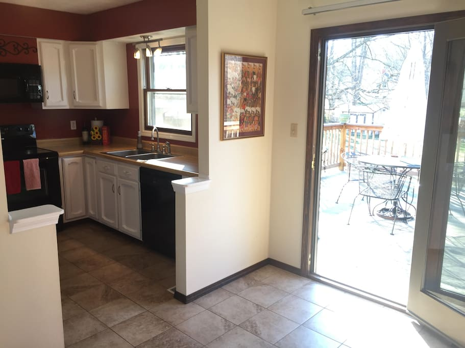 fully equipped kitchen with cooking necessities and new appliances attached to dining area that walks out onto back deck