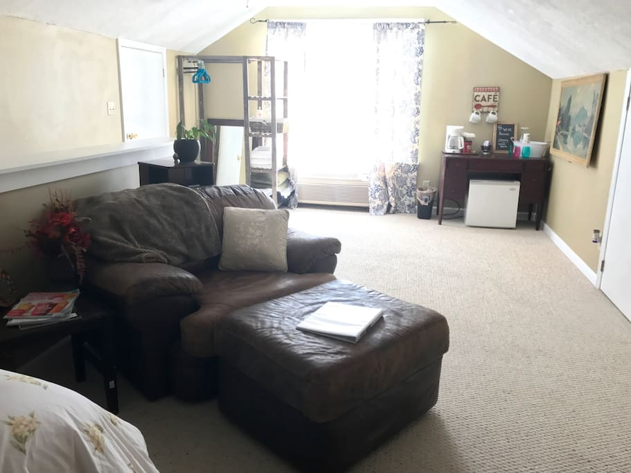 Sitting area in bedroom With mini fridge and coffee bar.