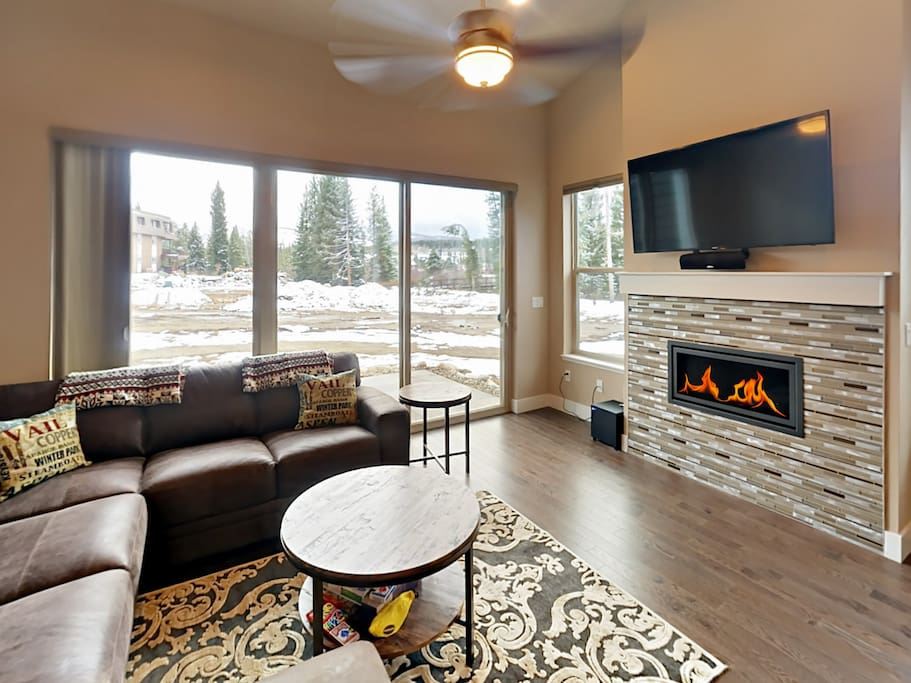 """Relax by the fireplace on the sectional sofa and enjoy the 55"""" TV with cable and a surround sound system."""