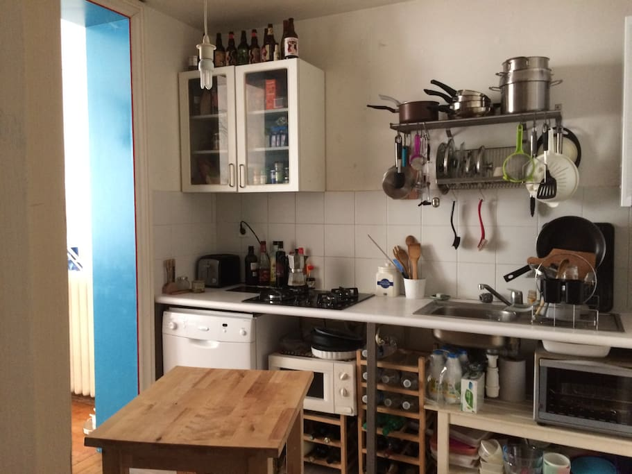 Vue de la cuisine : lave-vaisselle, four micro-ondes, four électrique, 4 plaques cuisson gaz, grille-pain. Il y a également un grand réfrigérateur avec compartiment congélateur.