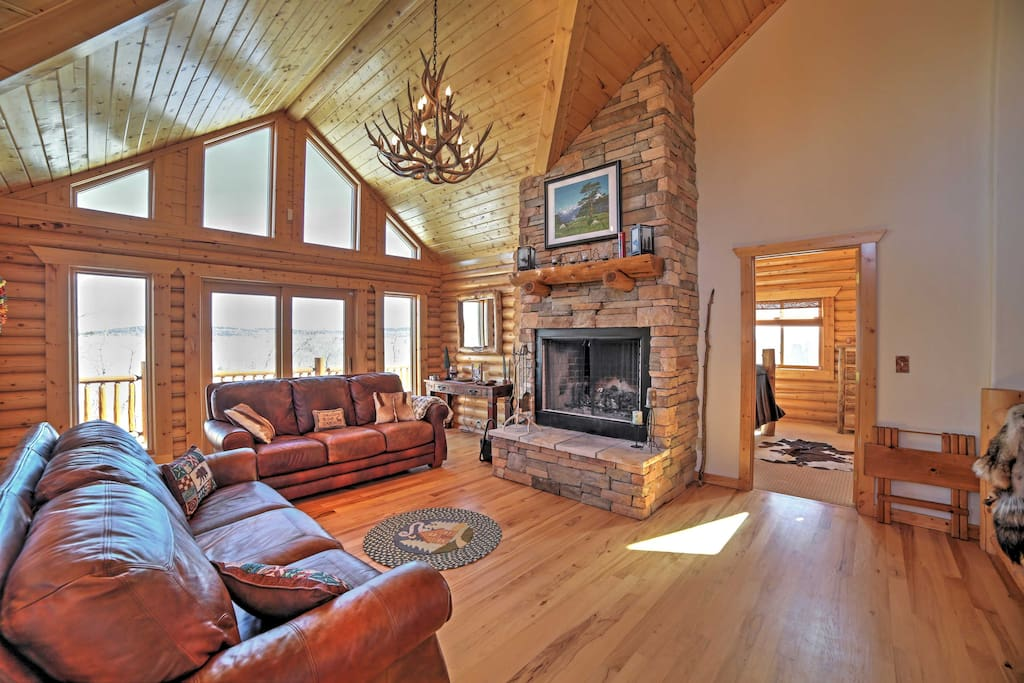 Cozy up next to the wood-burning fireplace on the plush leather couch and admire the surrounding natural beauty from the floor-to-ceiling windows.