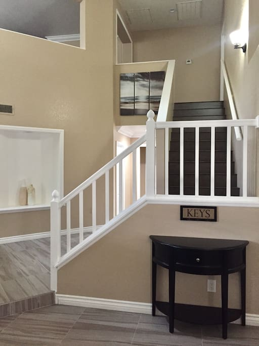 Initial sight upon entrance. Stairwell leading to the upper level of the house.