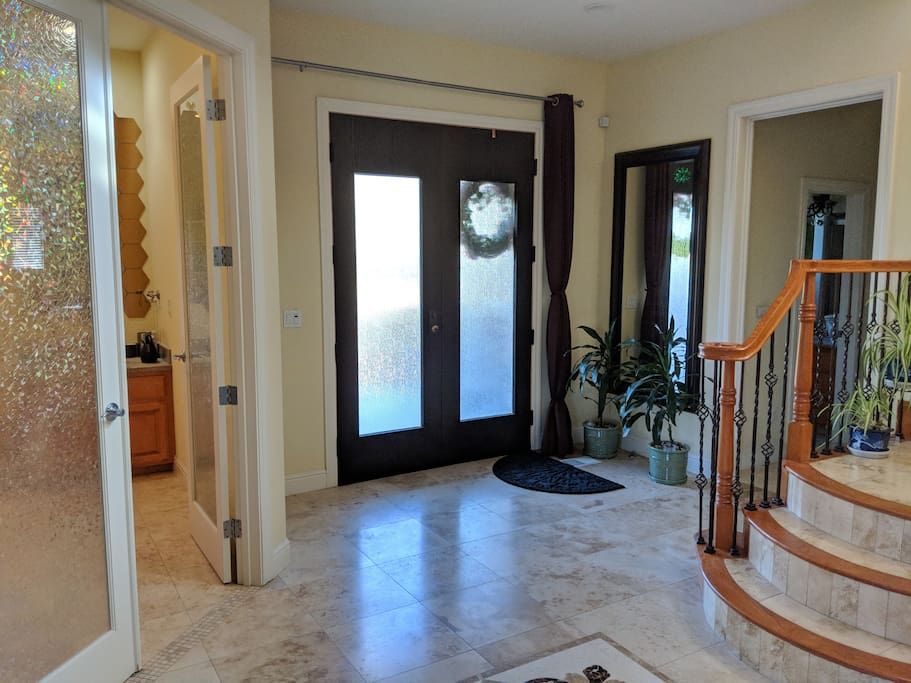 Just inside the front door, the floors are tiled travertine, granite, and marble. Your destination lies just up the stairs.
