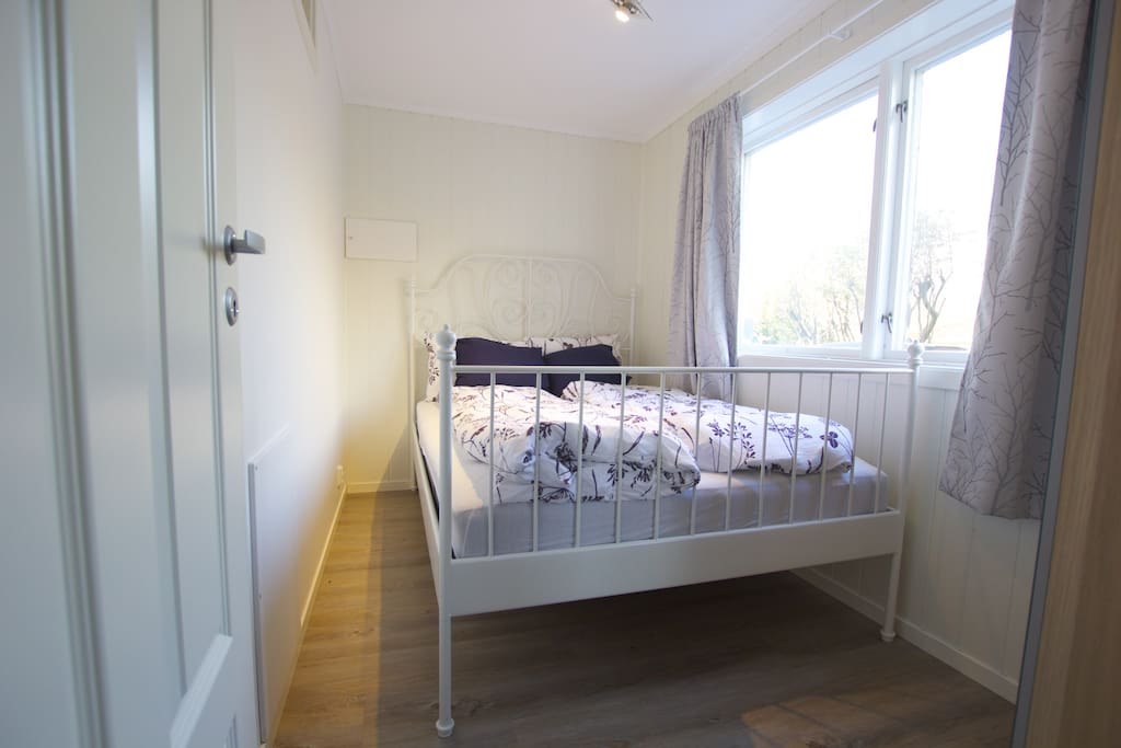 Cozy bed room, large windows, double bed and a wardrobe. Koselig soverom, store vinduer og et klesskap.