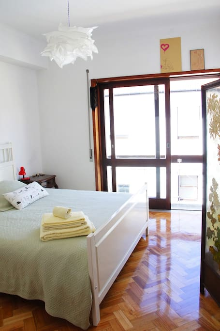 Bright bedroom with Queen sized bed and balcony over pedestrian street