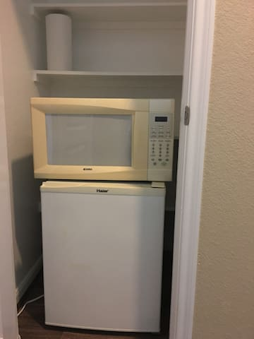 Small refrigerator and microwave for guest located inside the closet on left side of the bathroom.